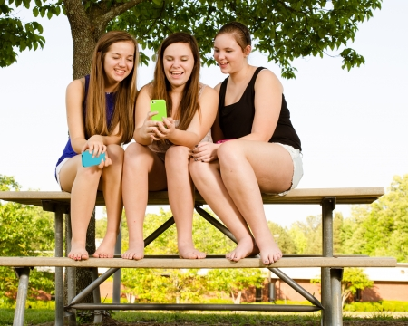 Young pre-teen girls texting while hanging out in front of their school photo