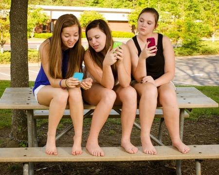 chicas adolescentes: Las niñas pre-adolescentes jóvenes mensajes de texto mientras colgando en frente de su escuela Foto de archivo