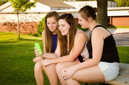 ni�a: Las ni�as pre-adolescentes j�venes mensajes de texto mientras colgando en frente de su escuela Foto de archivo