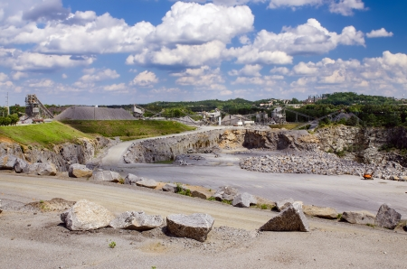 Working rock quarry under cloudy blue sky