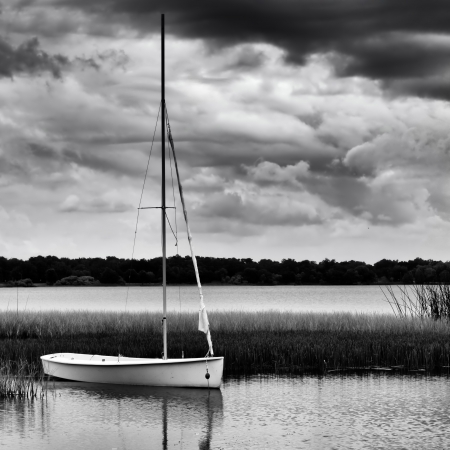 Sailboat anchored on lake during stormy day in monochrome image photo