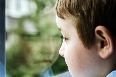 Trauriges Kind schaut aus Fenster auf düsteren Tag Standard-Bild - 20680040
