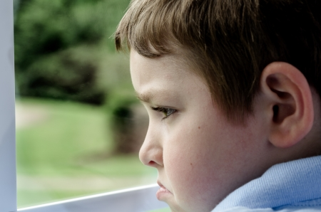 angry: Sad child looking out window on gloomy day