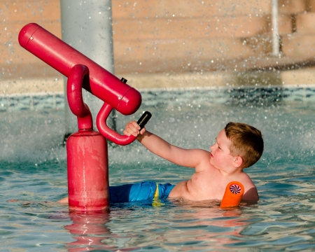 kiddie: Child playing with water cannon at kiddie pool during summer  Stock Photo
