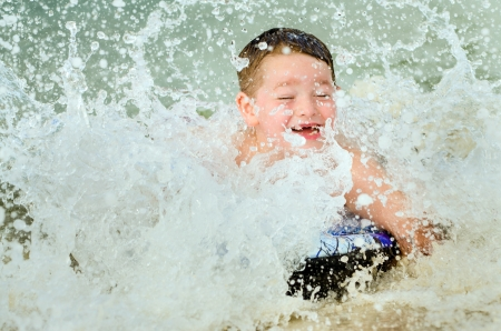Child surfing on bodyboard at beach photo