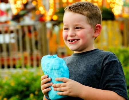 algodon de azucar: Ni�o feliz comiendo algod�n de az�car en el carnaval