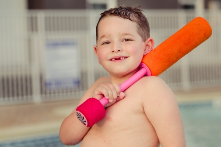 Happy child with his water toy at pool during summer photo