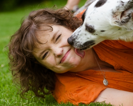 disgusted: Woman making disgusted face while being licked by her pet dog Stock Photo