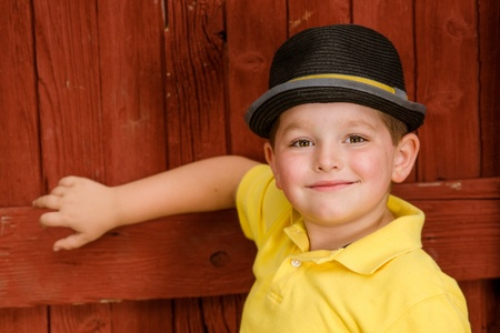 fedora hat: Portrait of child wearing fedora hat next to rustic barn