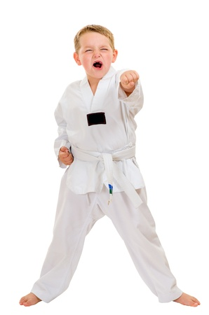 Child practicing his taekwondo moves isolated on white Фото со стока