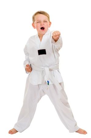 Kind beoefenen van zijn taekwondo moves geïsoleerd op wit