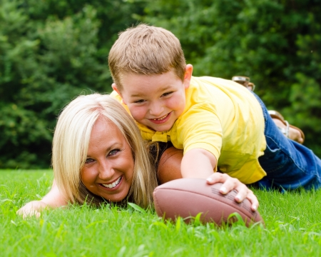 mother and son: Child tackling mom while playing football together outdoors