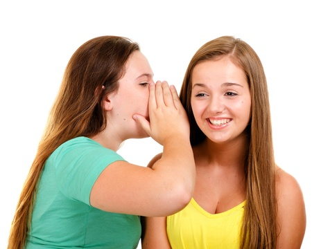 chit chat: Laughing teenage girls whispering and gossiping isolated on white