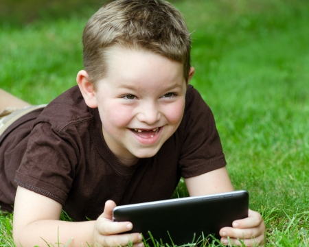 Child using tablet computer outdoors photo