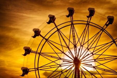 カウンティ フェアで夏の間に夕暮れ時の観覧車のシルエット