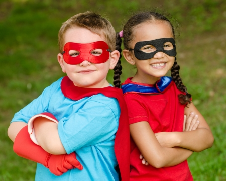 child couple: Pretty mixed race girl and Caucasian boy pretending to be superhero Stock Photo