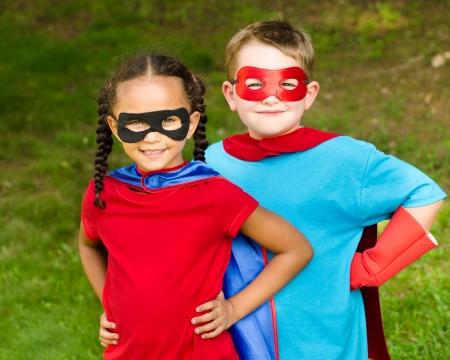 Pretty mixed race girl and Caucasian boy pretending to be superhero Standard-Bild