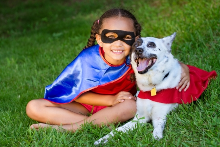 Pretty mixed race girl hugging her pet  with both dressed up in hero costumes Stock Photo