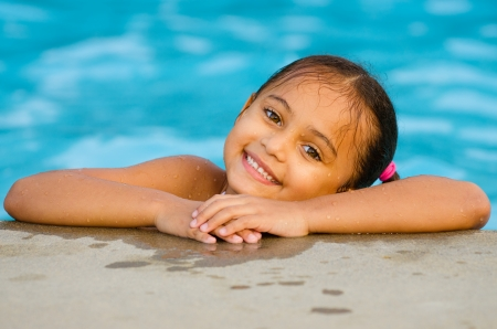 Portrait of happy pretty mixed race child by side of pool during summer photo