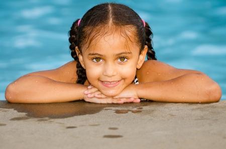 swimming race: Portrait of happy pretty mixed race child by side of pool during summer Stock Photo
