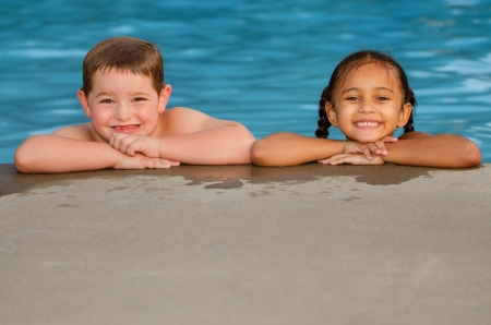 swimming race: Portrait of Caucasian boy and mixed race girl in pool after swimming and playing together