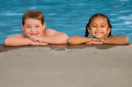 natacion: Retrato de muchacho de raza caucásica y niña de raza mixta en la piscina después de nadar y jugar juntos