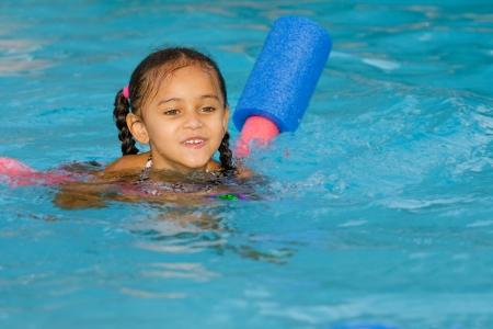 Pretty gemengd ras kind zwemmen in het zwembad in de zomer Stockfoto