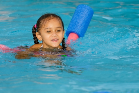 Pretty mixed race child swimming in pool during summer photo