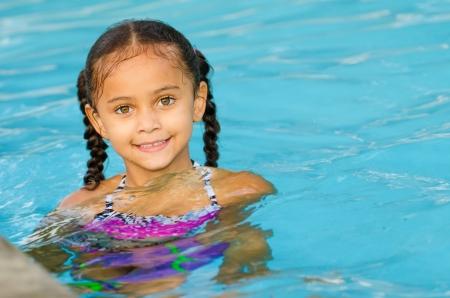 Portrait de l'heureux joli enfant de race mixte à côte de la piscine pendant l'été Banque d'images