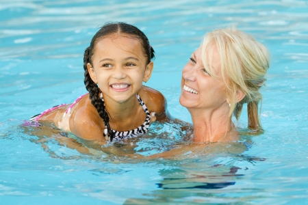 Moeder en een gemengd ras meisje spelen in zwembad tijdens de zomer