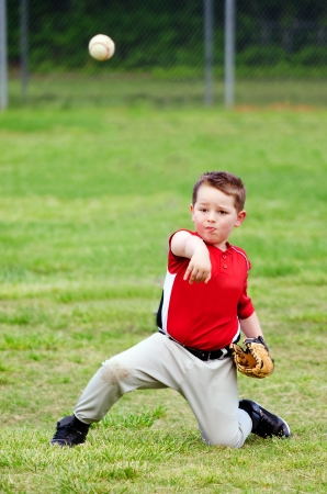 Child in uniform throwing baseball during game photo