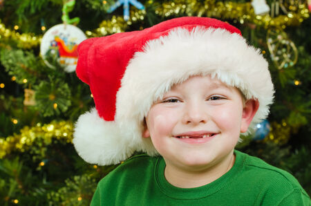 Christmas portrait of happy child wearing Santa hat in front of Christmas tree  photo