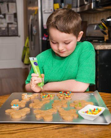 decorating: Child decorating ginger bread man Stock Photo