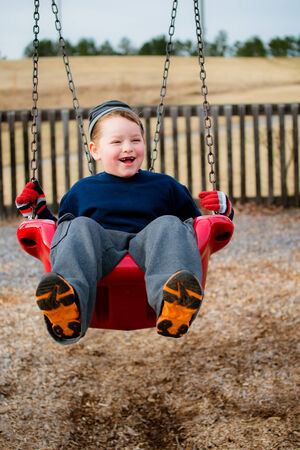 Happy child laughing while swinging at playground photo