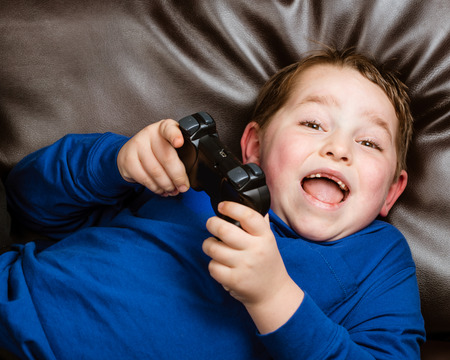 5 6 years: Young boy playing video game laying on couch at home Stock Photo