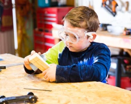 Boy schuren houten blok in de werkplaats als hij bouwt auto voor Pinewood Derby