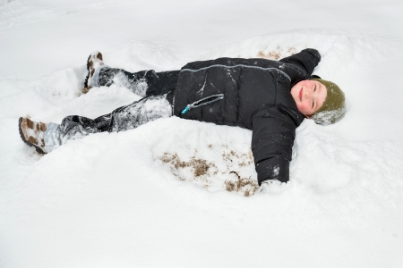 Child playing in snow by making snow angel photo