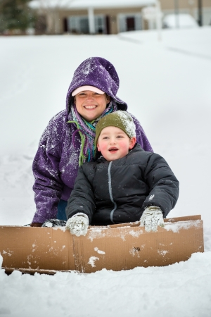 Mother and son playing in snow using cardboard box to slide down hill photo
