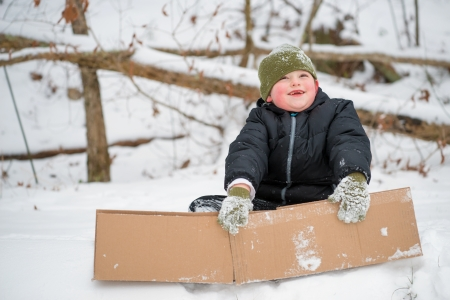 Child playing in snow using cardboard box to slide down hill photo