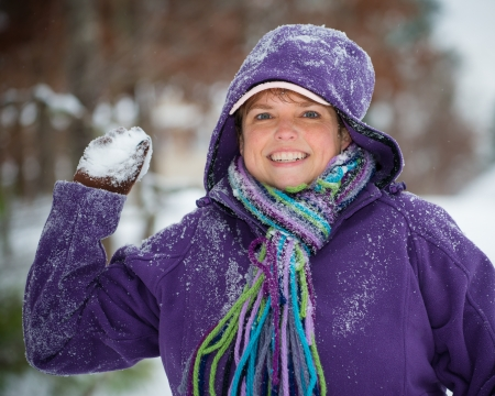 family fight: Woman playing in snow throwing snowball
