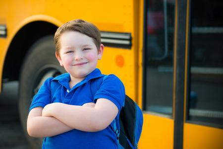 autobus escolar: Muchacho joven feliz en frente del autobús de la escuela volver a la escuela