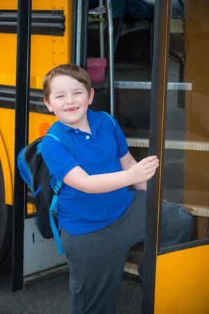 Happy child boarding school bus going back to school photo