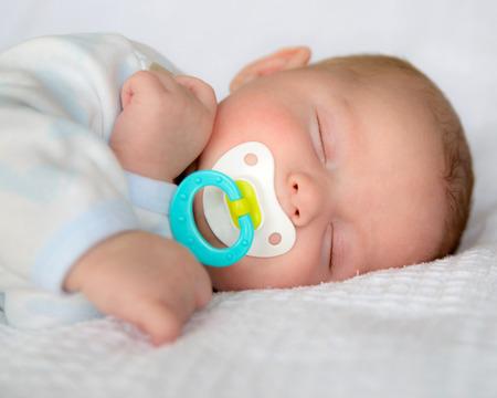 Baby baby jongen slapen rustig met fopspeen Stockfoto