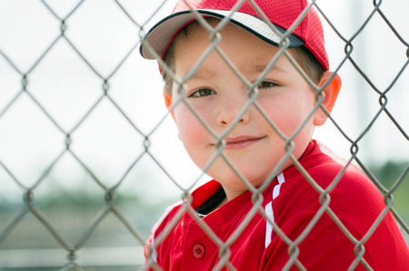 Young baseball player in uniform sitting in dugout Stock Photo