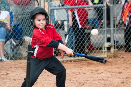 baseball swing: Young baseball player hitting ball off a tee during game