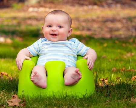 sit: Happy infant baby boy using training Bumbo seat to sit up Stock Photo