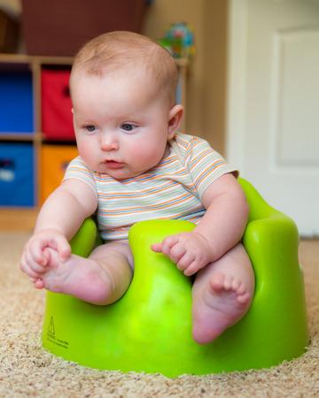 baby sit: Baby boy using training Bumbo seat to sit up