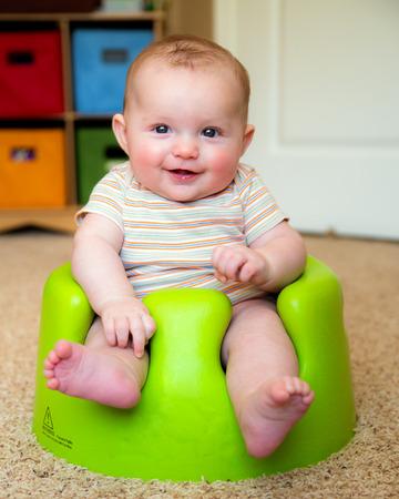 Baby boy using training Bumbo seat to sit up
