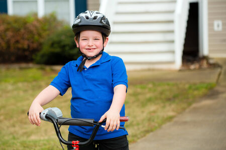 Happy child riding his bike outside his home 免版税图像