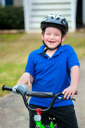 road cycling: Happy child riding his bike outside his home Stock Photo
